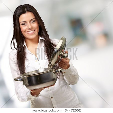 portrait of a young girl opening a sauce pan indoor