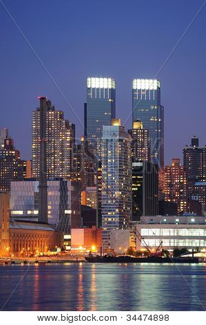 A group of urban modern architecture in New York City midtown Manhattan at dusk over river.