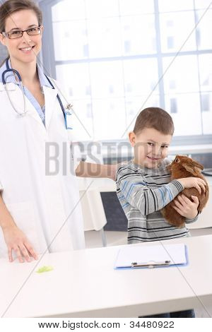 Smiling kid holding pet rabbit at veterinary office.