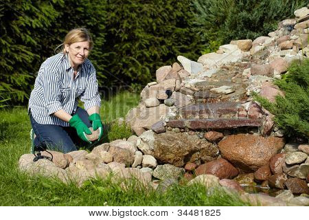Mature woman move stones around pond in her back garden