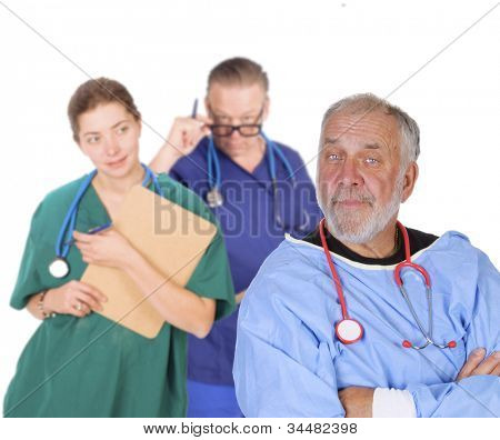 Portrait of an older doctor with arms folded looking smug, standing in front of his team smiling