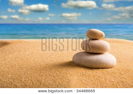 Macro of three staked zen stones on the beach