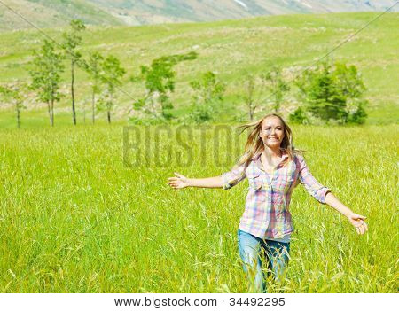 Young happy woman walking on wheat field, cute teen runs on green grass field, carefree girl enjoying peaceful countryside nature, beautiful smiling female have recreation in park, freedom concept