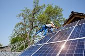 Bottom View Of Two Technicians On Metal Platform Installing Solar Photo Voltaic Panels On Bright Sun poster