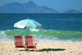 Pair Of Empty Red Beach Chairs With Light Blue Parasol On The Sandy Beach Against The Crashing Waves poster