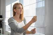 Pretty, young woman lowering the interior shades/blinds in her modern interior apartment poster