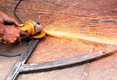 picture of friction  - Mechanic using a electrically operated sawing machine to smooth the rough edges of a welded iron bar and sparks flying out because of extreme friction between the machine and the metal - JPG