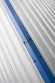 Metal Corrugated Sheets On A Building With A Blue Metal Corners. White Aluminium Metal Corrugated Ro poster