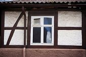 Window on facade of old half-timbered house in Bodenwerder, Germany.                                 poster