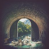 Digital Photo Manipulation Of An Alpine Mountain Stream Running Through An Old Arched Brick Tunnel.  poster