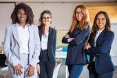 Group Of Confident Young Women Looking At Camera. Beautiful Smiling Businesswomen Posing In Modern O poster