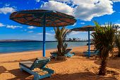 Sun Umbrellas And Chaise Lounges On Tropical Beach. Concept Of Rest, Relaxation, Holidays, Resort poster