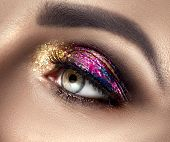 Beautiful Eye Make-up with colorful sparks. Beauty bright fashion holiday smoky eye makeup. Make up  poster