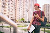 Young man  stands with backpack and holds smartphone, in the city.   Teenage boy is using mobile pho poster