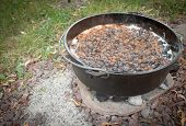 stock photo of dutch oven  - Blueberry cobbler cooking in the dutch oven with charcoals to heat it from underneath - JPG