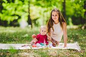Young Pretty Mother With Daughter Lie On A Plaid In The Park. Family Outdoor Recreation. Family Summ poster