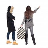 back view of two women with shopping bags in winter jacket. backside view of person. Rear view peopl poster