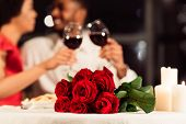 Valentines Romantic Date. Red Roses Lying On Table, Unrecognizable Spouses Drinking Wine In Restaura poster