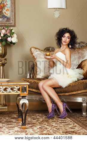 Luxurious Lady Sitting On Retro Couch With Cap Of Coffee. Classic Interior