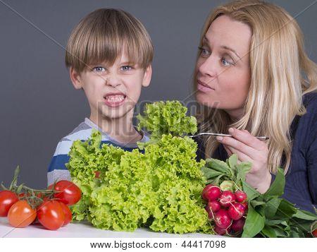 Mutter, die versucht, einen jungen zu ernähren, der frischen Salat nicht mag