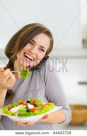 Smiling Young Woman Eating Salad And Talking Mobile Phone