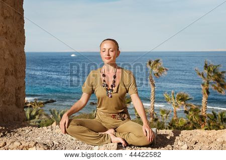 Young woman meditating near the sea