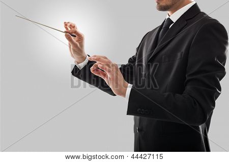 Orchestra conductor directing with his baton