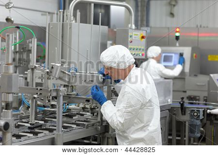 two workers at production line in plant