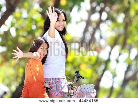Two Girls Riding Bicycle