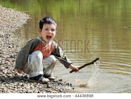 Child playing with stick in water