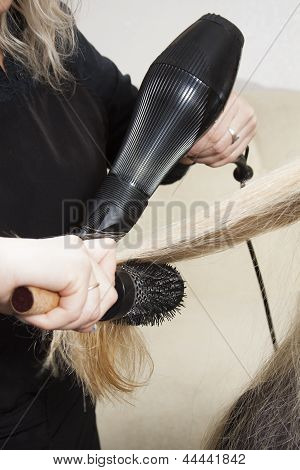 Hairdressers hands drying long blond hair