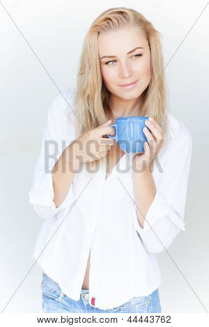 Beautiful blond woman holding blue coffee cup in hands isolated on white background, having morning drink at home
