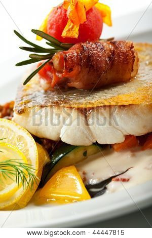 Fried Fish (Zander) with Bacon. Garnished with Lemon,  Lentil and Vegetables
