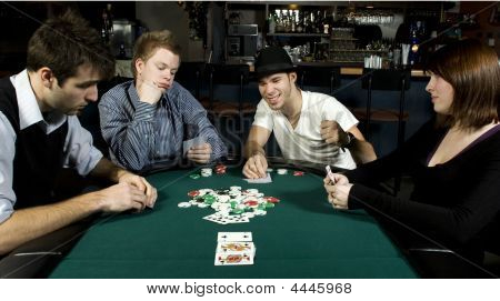 Four Friends Around Table Playing Poker