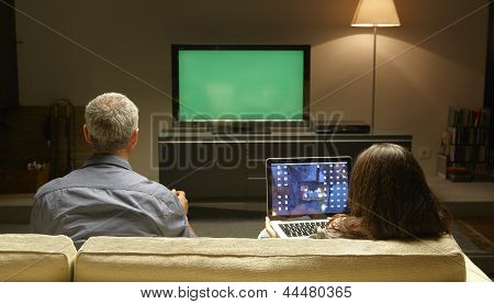 Mid Adults Watching Tv And Pc