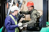 stock photo of forklift  - Young forklift driver communicating with supervisor at warehouse - JPG
