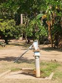 stock photo of groundwater  - A standing Old rusty groundwater pump in nature - JPG