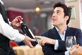 Waiter suggesting a bottle of wine to a customer