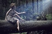 stock photo of nymphs  - Sexy Woman Sitting On  Tree in forest - JPG