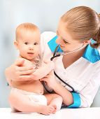 Baby And Doctor Pediatrician. Doctor Listens To The Heart With Stethoscope