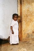 picture of girl next door  - Cute but sad little black African girl in pink sunday dress next to her home door made of fabric - JPG