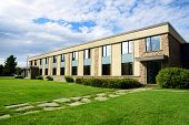 foto of entryway  - Small office or business building or college school perspective shot with sky and grass - JPG