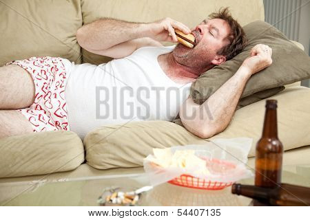Unemployed middle aged man at home on the couch in his underwear, eating a hamburger,  with a marijuana joing in the ashtray and beer bottles lying around.
