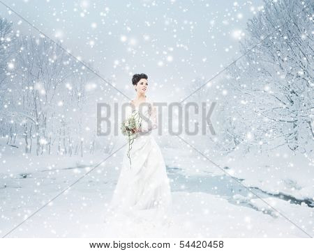 Young and beautiful bride with the flower bouquet in winter forest