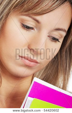 Close up on young sad student holding workbook, documents.