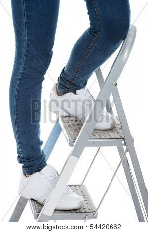 Woman in jeans on a step ladder. Isolated on white.