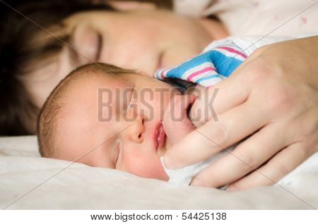 Newborn infant child resting next to mother after delivery at hospital