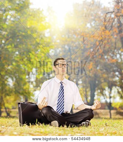 Young businessperson seated on a green grass meditating in a park on a sunny day, shot with a tilt and shift lens