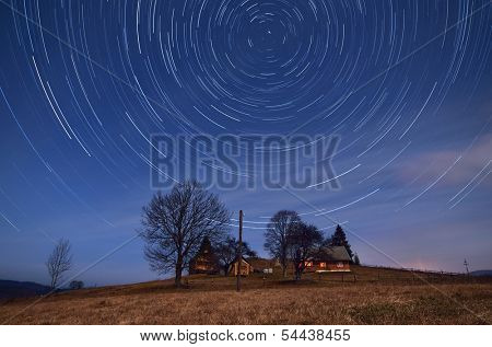 Night landscape with star tracks. Mountain village with wooden houses. Carpathians, Ukraine, Europe