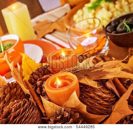 Closeup photo on beautiful autumnal still life for Thanksgiving day, pine cone and dry leaves decoration for festive dinner